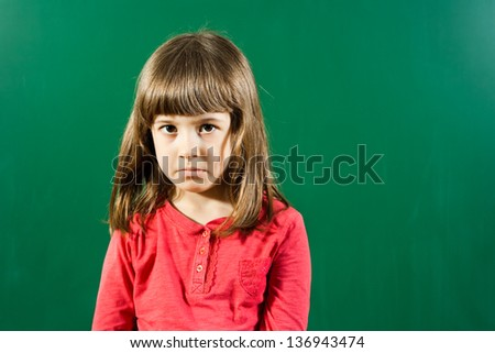 Little girl with sad expression in front of blackboard,Sad little girl - stock photo