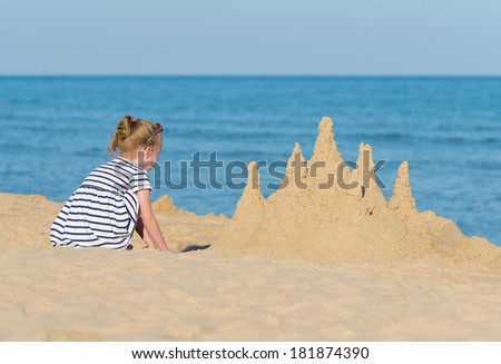 Little girl with sand castle on the beach. - stock photo