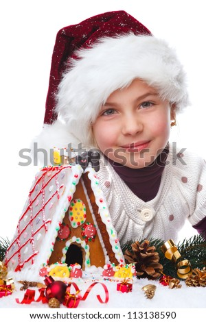 little girl with santas hat and gingerbread house - stock photo