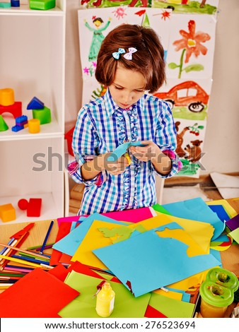 Little girl with  scissor  at school. Child picture on background. - stock photo