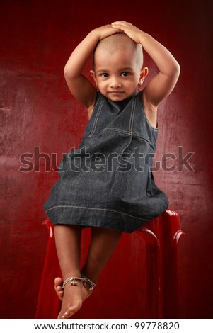 Little girl with shaved head shows a funny gesture in a red background - stock photo