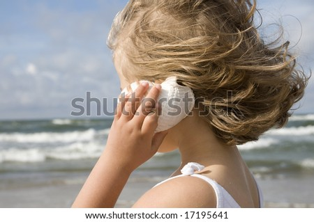Little girl with shell on the beach - stock photo