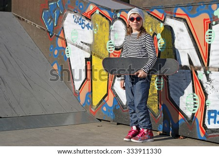 little girl with skateboard in skate park - stock photo