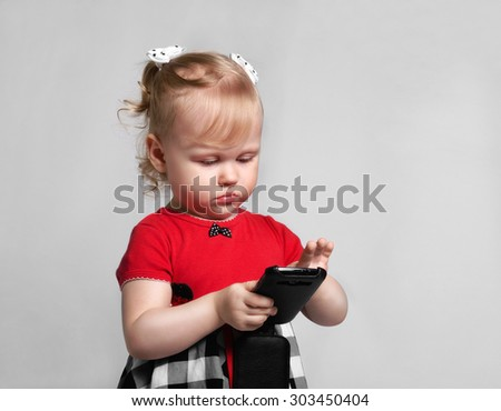 little girl with smartphone look screet photo studio - stock photo