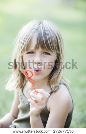 little girl with soap bubbles having fun outdoors. Looking at the camera  - stock photo