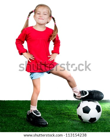 little girl with soccer ball in boots on a green lawn - stock photo
