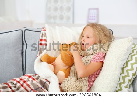 Little girl with sore throat holding toy bear closeup - stock photo