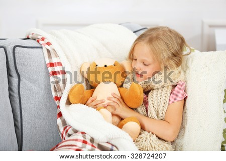 Little girl with sore throat holding toy bear closeup