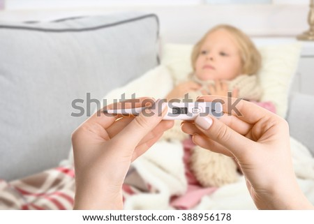 Little girl with sore throat lying in bed and hands with thermometer - stock photo