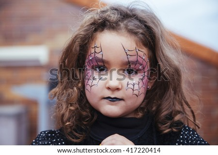 Little girl with spider web painted on face looking at camera. Halloween - stock photo