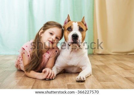 Little girl with staffordshire terrier dog - stock photo