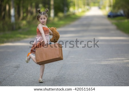 Little girl with suitcase and Teddy bear on the road. - stock photo