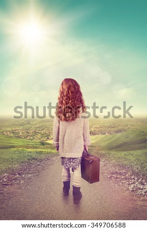 Little girl with suitcase at country road - stock photo