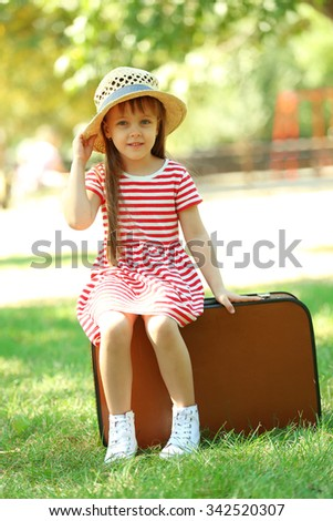 Little girl with suitcase in the park