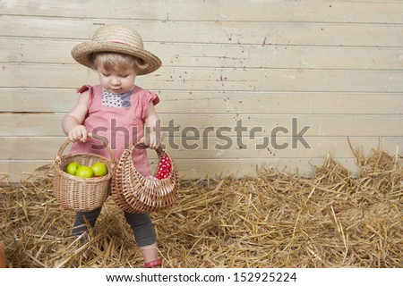 Little girl with summer straw hat in a barn with straw - stock photo