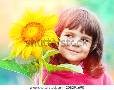 Little girl with sunflower - stock photo