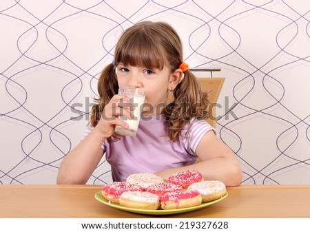 little girl with sweet donuts and milk breakfast - stock photo