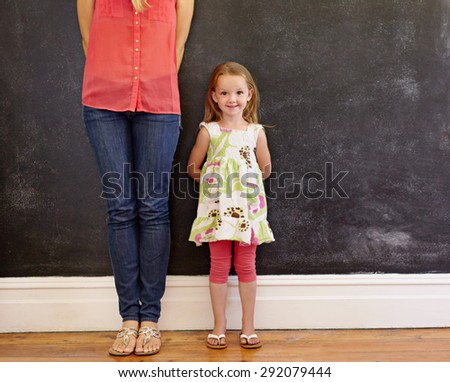 Little girl with sweet smile standing with her mother. Mother is cropped in the picture with focus on little girl looking at camera. Both standing by a wall with copy space. - stock photo