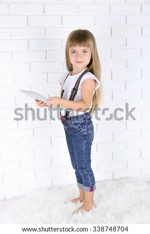 Little girl with tablet on brick wall background - stock photo