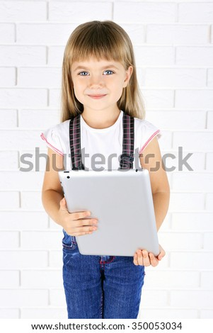 Little girl with tablet on brick wall background