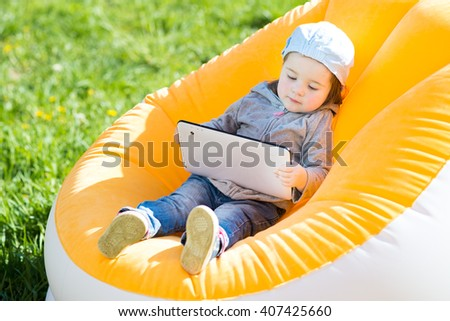 Little girl with tablet on the inflatable chair in the garden