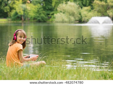 Little girl with tablet pc and headphones listening to music or watching video at lakeside. Child have rest near water in park.
