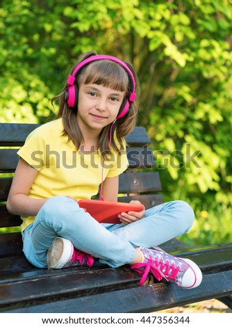Little girl with tablet pc and headphones sitting on the bench and listening to music or watching video in summer park - stock photo