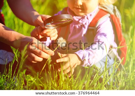 Little girl with teacher examining field flowers using magnifying glass - stock photo