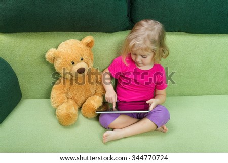 Little girl with Teddy bear, and a tablet. Sitting on a green couch. - stock photo