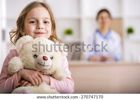 Little girl with teddy bear is looking at the camera. Female doctor on background. - stock photo
