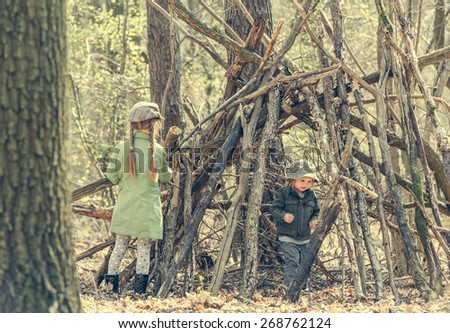 little girl with ter sister  in the wood near the hut. Photo in retro style - stock photo