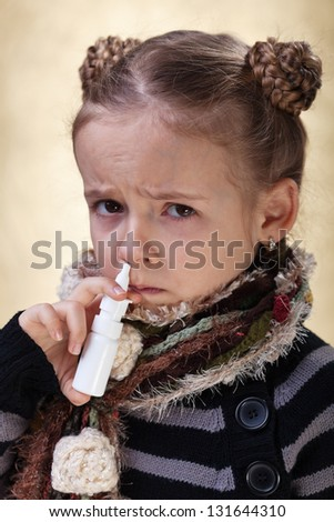 Little girl with the flu using nasal spray reluctantly - stock photo