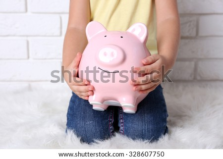 Little girl with the pig  moneybox on brick wall background - stock photo