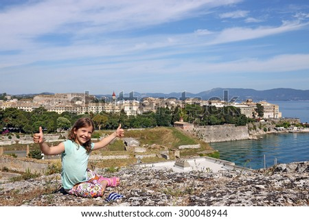 little girl with thumbs up in Corfu town Greece