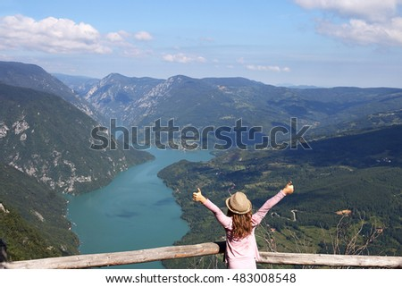 little girl with thumbs up standing on mountain viewpoint