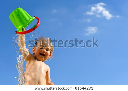 Little girl with toy bucket, poured water - stock photo