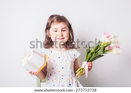 Little girl with tulips and box with present for mom