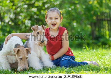 Little girl with two dogs of breed fox terrier on green lawn - stock photo