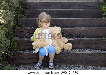 little girl with two teddy bears seated on wooden steps - stock photo