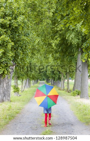little girl with umbrella in spring alley - stock photo