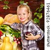 Little girl with vegetable on kitchen. - stock photo