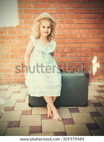Little girl with vintage suitcase. Travel concept. Retro tinted photo - stock photo