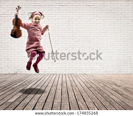 little girl with violin jumping on a room with white bricks wall and wood floor - stock photo