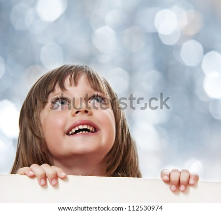 little girl with  white board with empty space - bokeh background - stock photo