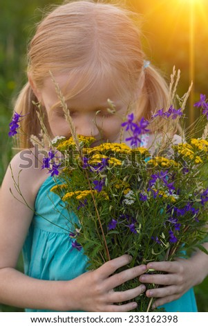 little girl with wild flowers  - stock photo