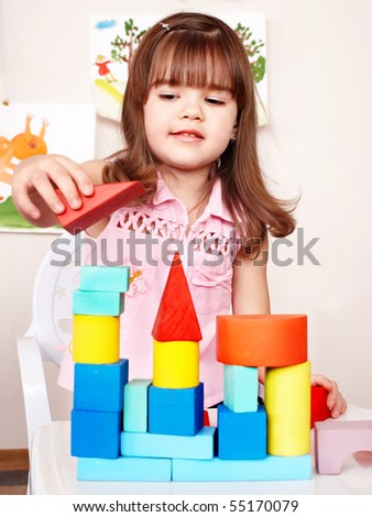 Little girl with wood block in play room. - stock photo