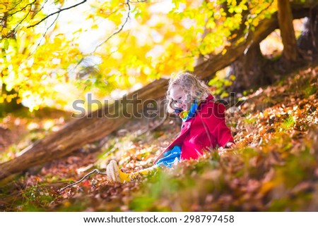 Little girl with yellow leaf. Child playing with autumn golden leaves. Kids play outdoors in the park. Children hiking in fall forest. Toddler kid under a maple tree on a sunny October day. - stock photo