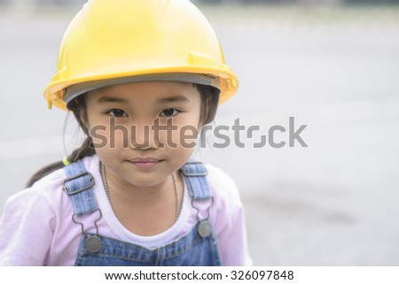 Little girl with yellow safety helmet in blur warehouse center background