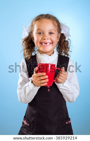 Little Girl Without Teeth Holding A Red Cup Isolated On Blue Background - stock photo