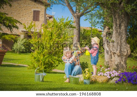 Little girl working with her mother in the garden